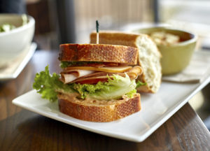 Turkey sandwich with bacon cheese lettuce tomato and mayonaise on wheat bread with soup