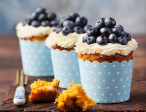 Pumpkin cupcakes decorated with cream cheese frosting and fresh blueberries on a wooden background Copy space